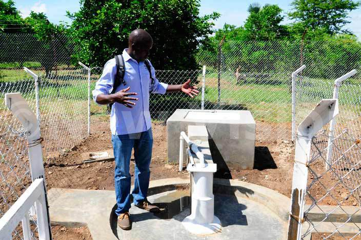 Julius Olobo, the area manager Drop in the Bucket teaches a blind pupil how to use the newly installed water-borne toilets at Madera School for the Blind