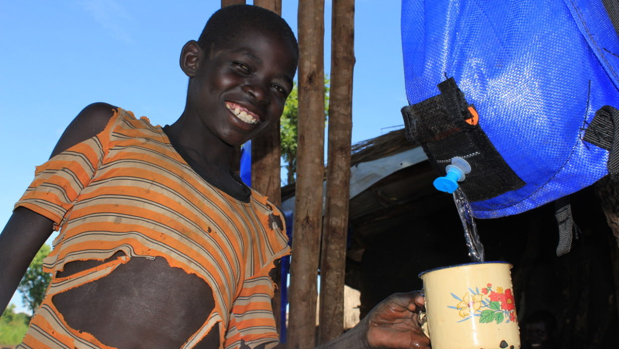 A South Sudanese refugee child getting clean water from a Pack H2O water backpack in Uganda