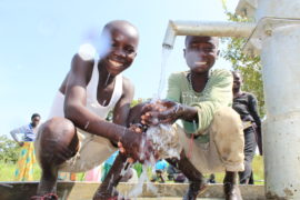 Two children getting clean drinking water from a well in Koboko, Uganda drilled by US water charity Drop in the Bucket