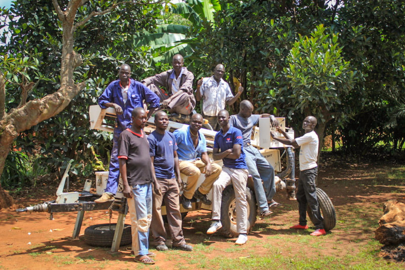Drop in the Bucket staff sit on a Pat 301T drilling rig in Uganda after completing drilling a new water well in Koboko.