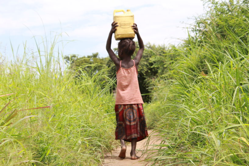 Young girl with water jug on her head in Uganda showing importance of World Water Week