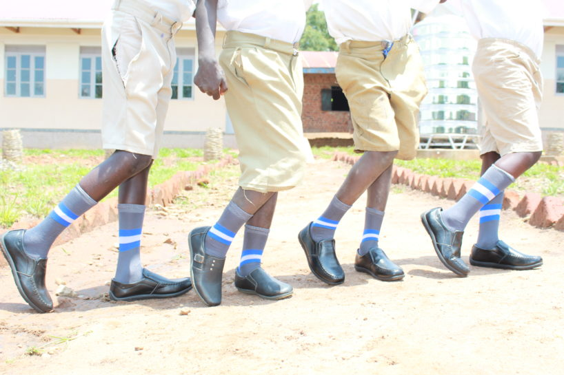 Four boys in Uganda show of their new shoes