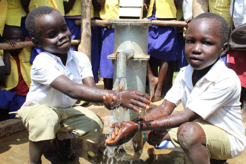 School children in Uganda gather round two boys using a clean water well from Drop in the Bucket