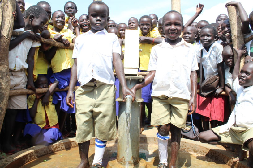 School children in Uganda gather round two boys who share a pair of shoes