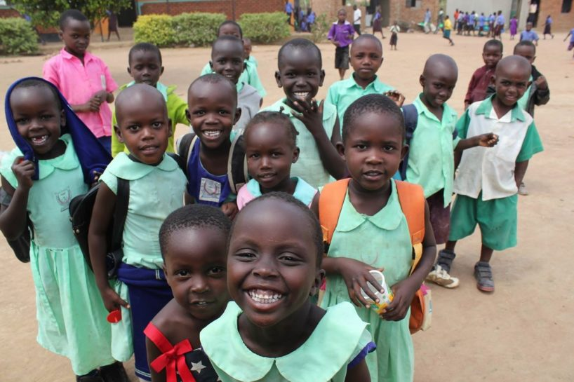 A group of young students in Uganda with green uniforms are smiling