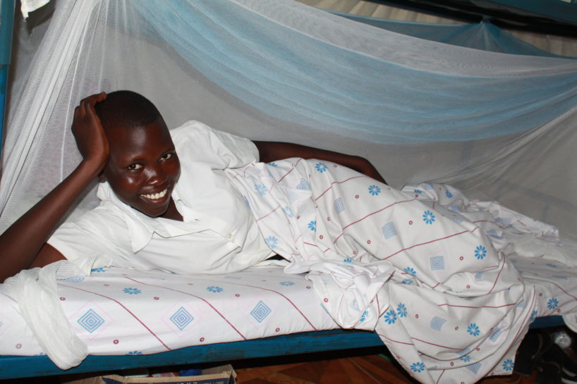 A young female student lays down in her dorm bunk in Uganda