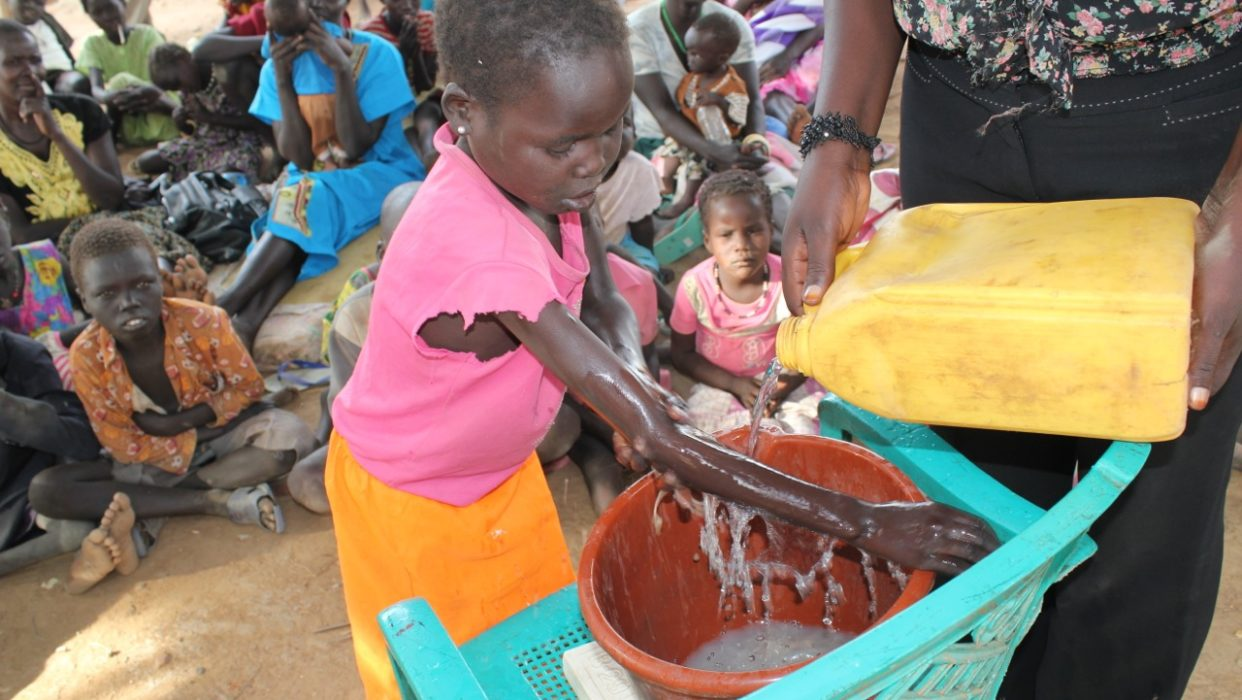 Drop in the Bucket hygiene and sanitation trainers teaching effective hand washing to South Sudanese refugee children.